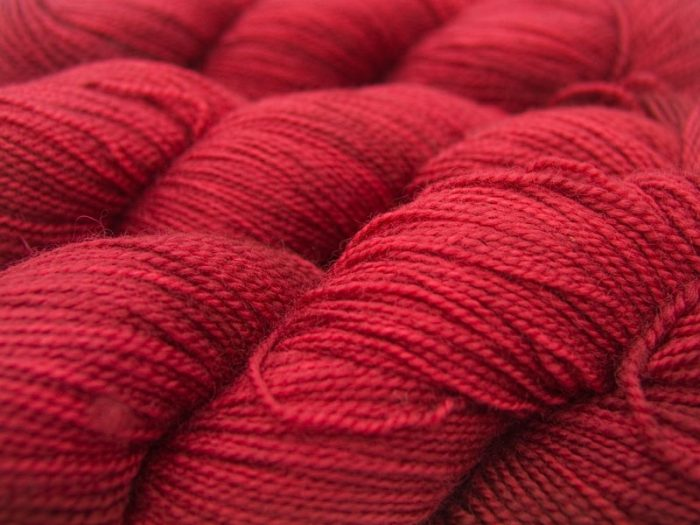 Semi-solid deep red superwash Bluefaced Leicester (BFL) 4-ply/fingering/sock yarn. Hand-dyed by Triskelion Yarn