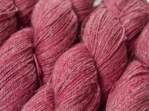 Semi-solid deep rose Baby Alpaca, silk and linen 4-ply yarn. Hand-dyed by Triskelion Yarn.
