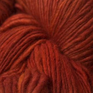 Semi-solid fiery orange Corriedale thick and thin slub yarn. Hand-dyed by Triskelion Yarn.