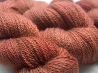 Autumnal orange-brown with red and dark brown variations Bluefaced Leicester (BFL) / Masham aran yarn. Hand-dyed by Triskelion Yarn
