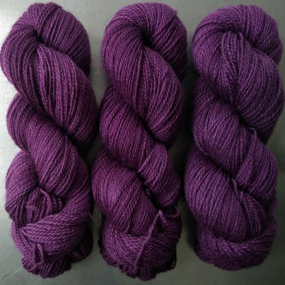 Semi-solid dark purple, with red-violet and royal purple tones Bluefaced Leicester (BFL) / Gotland 4-ply (fingering) yarn. Hand-dyed by Triskelion Yarn