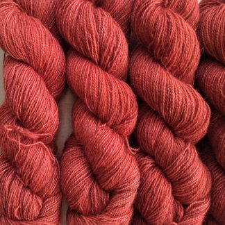 Rowanberry - Mid-tone coral vermilion Bluefaced Leicester (BFL) / Gotland / Wensleydale 4-ply (fingering) weight high-twist sock yarn. Hand-dyed by Triskelion Yarn