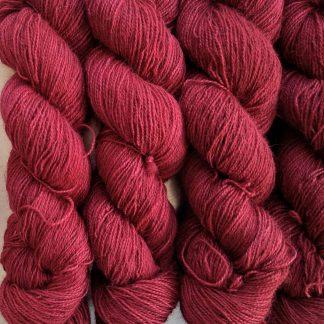 Wyrd - Deep cherry red Bluefaced Leicester (BFL) / Gotland / Wensleydale 4-ply (fingering) weight high-twist sock yarn. Hand-dyed by Triskelion Yarn