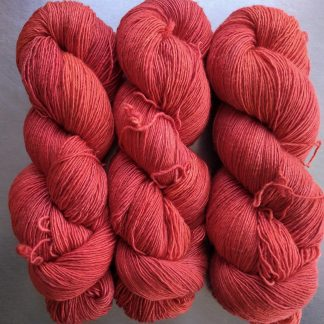 Coral - Strong pinkish orange Falklands Merino and silk blend yarn. Hand-dyed by Triskelion Yarn.