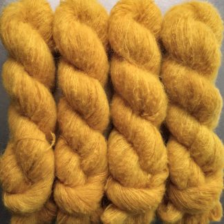 Mango - Warm imperial yellow suri alpaca and silk luxury heavy laceweight yarn. Hand-dyed by Triskelion Yarn
