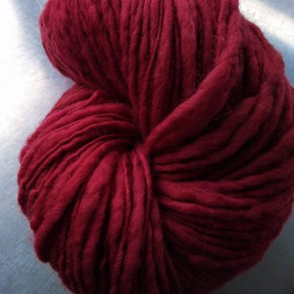 Chilli - Mid-tone red Corriedale thick and thin slub yarn. Hand-dyed by Triskelion Yarn