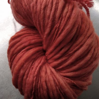 Coral - Mid-tone pinkish orange Corriedale thick and thin slub yarn. Hand-dyed by Triskelion Yarn