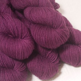 Tyrian Purple - Dark reddish purple Bluefaced Leicester worsted weight yarn hand-dyed by Triskelion Yarns