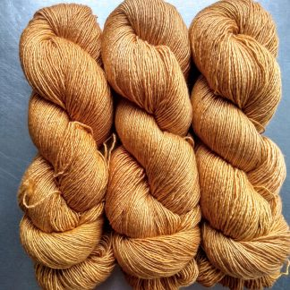 Anemone - Light orange with a yellow undertone Falklands Merino and silk blend yarn. Hand-dyed by Triskelion Yarn.