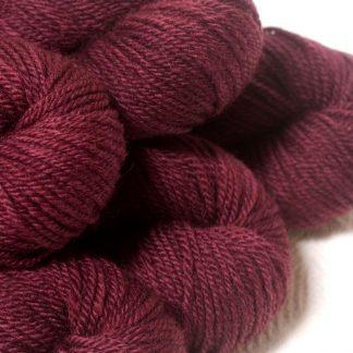Damson - Mid-tone violet red Bluefaced Leicester (BFL) / Masham aran yarn. Hand-dyed by Triskelion Yarn