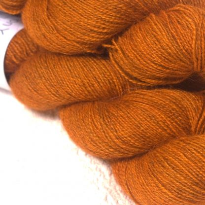 Mid tone autumnal orange Bluefaced Leicester (BFL) / Gotland / Wensleydale 4-ply (fingering) weight high-twist sock yarn. Hand-dyed by Triskelion Yarn