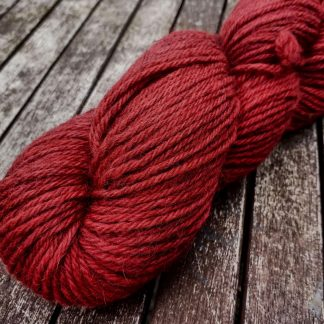 Exocarp - Mid to dark scarlet Bluefaced Leicester (BFL) / Gotland aran weight yarn. Hand-dyed by Triskelion Yarn