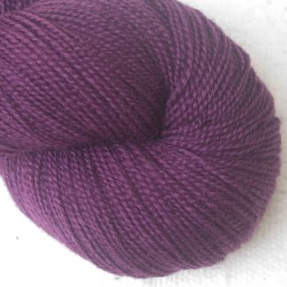 Helleborine - Dark Tyrian red-purple Corriedale 4-ply/fingering weight yarn. Hand-dyed by Triskelion Studio.